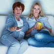 Mother with adult daughter watching television — Stock Photo #25547573