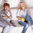 Mother with adult daughter watching television — Stock Photo #25547609