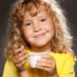 Little girl eating yogurt — Stock Photo