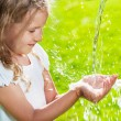 Stream of clean water pouring into children's hands — Stock Photo #29214991