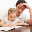 Father helping daughter doing homework — Stock Photo