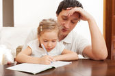 Father helping daughter doing homework — 图库照片