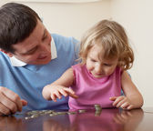 Dad and daughter puts coins — Стоковое фото