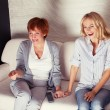 Mother with adult daughter watching television — Stock Photo #32520547