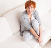 Happy mature woman on sofa — Stockfoto