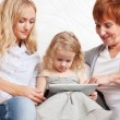 Family wiht tablet computer at sofa — Stock Photo