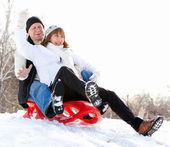 Mature couple sledding — Stock Photo