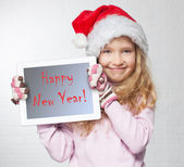 Child in christmas hat with tablet — Foto Stock