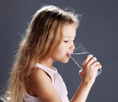 Girl drinking water from glass — Stock Photo