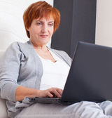 Mature woman with laptop — Stock Photo