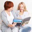 Mother and daughter looking photo book — Stock Photo
