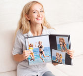 Young woman showing photo book — Stock Photo