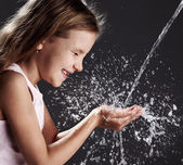Stream of clean water pouring into children's hands — Стоковое фото