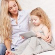 Mother and daughter wiht tablet at sofa — Stock Photo