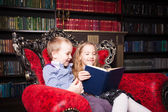 Children reading book at home — Stock Photo