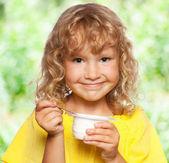 Little girl eating yogurt at summer — Foto Stock