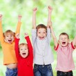 Happy children with their hands up — Stock Photo