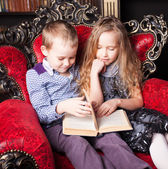Children reading book at home — Stock fotografie