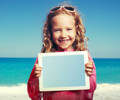 Child on the beach with tablet  pc — Stock Photo