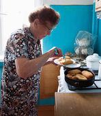 Elderly woman on the kitchen — Stockfoto