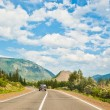 The car is driving on the road passing between the mountains — Stock Photo #22583043