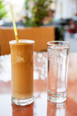 Glasses of frappe coffee and water — Stock Photo