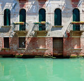 Front of old venetian house standing in water — Stock Photo