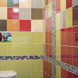 Fragment of a simple toilet room with multicolor walls — Stock Photo