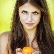 Beautiful woman holding tangerine — Stock Photo #10739905