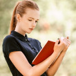 Young woman in dark blouse reads red book — Stock Photo #12609032