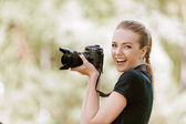 Smiling young woman photographs on camera — Stockfoto