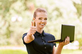Young woman keeps your laptop and lifts thumb up — Stock Photo