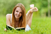 Young woman lying on grass and reading book — Stock Photo