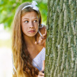 Frightened teenage peeping from behind tree - Stock Photo