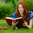 Young woman lying on grass with book — Stock Photo