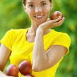 Young woman in yellow blouse with red apples — Stock Photo