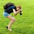 Smiling young woman photographs on camera - Stock Photo