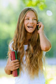 Teenage girl with books talking on mobile phone — Stock Photo