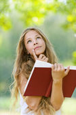 Teenage girl reading red book — Stock Photo