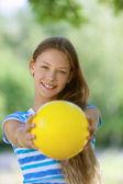 Smiling teenage girl holding yellow ball — Stock Photo