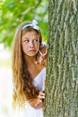 Frightened teenage peeping from behind tree — Stock Photo