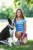 Teenage girl and black dog — Stock Photo