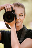 Smiling young woman photographs on camera — Photo