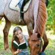 Stock Photo: Young womreading book with horse