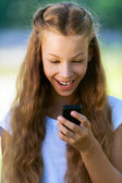 Teenage girl reading funny message on phone — Stock Photo