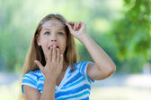Teenage girl with her hand covers mouth in amazement — Stock Photo