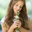 Smiling beautiful teenage with bouquet of daisies — Stock Photo #13180965