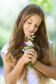 Smiling beautiful teenage with bouquet of daisies — Stock Photo