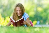 十几岁的女孩躺在草和阅读的书 — 图库照片