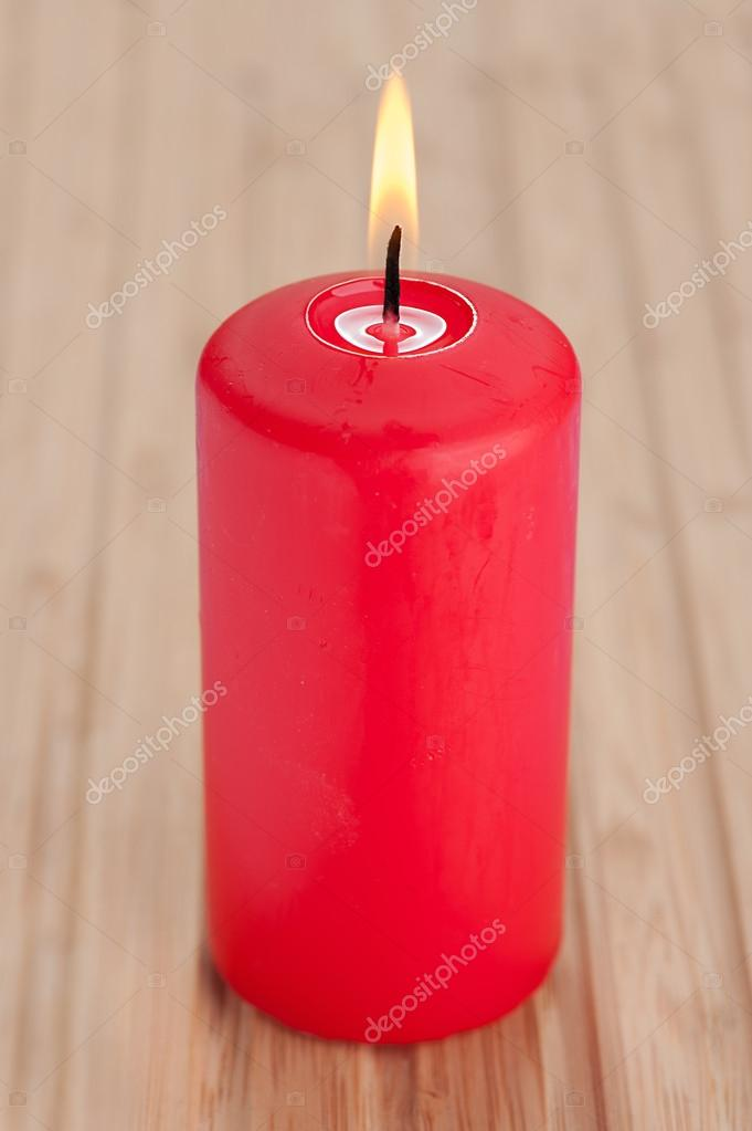 Red burning candle standing on wooden table.  Foto Stock #13180709